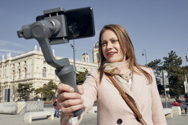Austria, Vienna, portrait of smiling young woman using selfie-stick for taking photo with smartphone - ZEDF01939