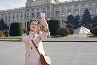 Austria, Vienna, portrait of smiling young woman taking selfie with smartphone - ZEDF01942