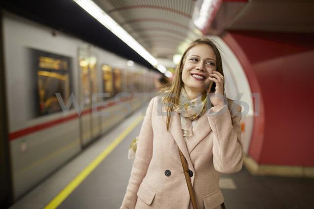 Austria, Vienna, portrait of smiling young woman on the phone at underground station platform - ZEDF01945 - Zeljko Dangubic/Westend61