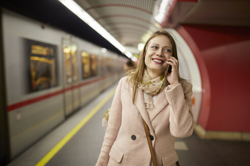 Austria, Vienna, portrait of smiling young woman on the phone at underground station platform - ZEDF01945