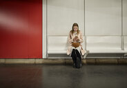 Austria, Vienna, young woman waiting at underground station using smartphone - ZEDF01948