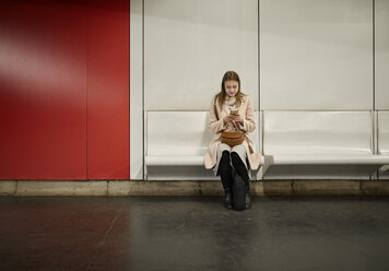 Austria, Vienna, young woman waiting at underground station using smartphone - ZEDF01948