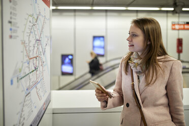 Austria, Vienna, smiling young woman looking at map at underground station - ZEDF01951