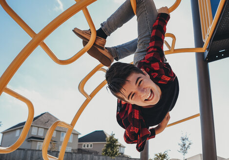 Portrait of carefree cheerful boy hanging from metallic steps at playground during summer - CAVF61995