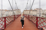 Confident woman with blond hair walking on Paul-Couturier Footbridge over Saone River against buildings in city - CAVF62025