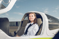 Portrait of confident female pilot sitting in airplane against blue sky at airport - CAVF62034