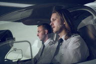 Side view of male pilot with trainee flying in flight simulator - CAVF62058