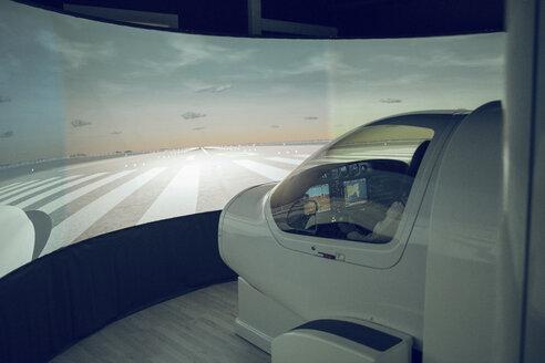 Side view of male trainee flying flight simulator seen through windshield - CAVF62061