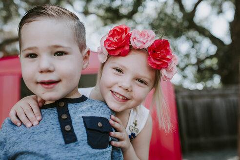 Portrait of cute smiling siblings standing against red garage in yard - CAVF62070