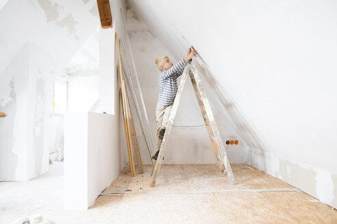 Deutschland, NRW, Haus, Baustelle, Dach, Dachboden, Holz, Leiter, Dachausbau, Dachschraege, Junge steht auf Holzleiter und misst mit Zollstock Wand aus - MFRF01168