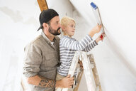 Father and son working on loft conversion using water level - MFRF01171
