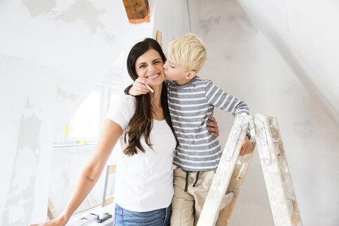 Portrait of happy mother and son working on loft conversion - MFRF01177