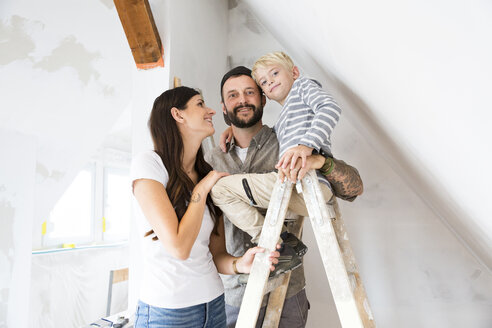 Portrait of happy family working on loft conversion - MFRF01180
