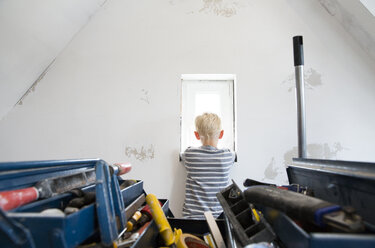 Boy looking out of window in attic to be renovated with toolbox in foreground - MFRF01186