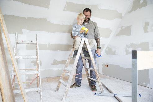 Deutschland, NRW, Haus, Baustelle, Dach, Dachboden, Holz, Dachausbau, Dachschraege, Portrait, Junge sitzt auf Leiter mit einer Rolle Klebeband in der Hand, Vater steht hinter ihm - MFRF01189