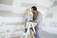 Father looking at son on ladder with taped mouth - MFRF01192