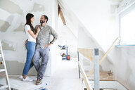Smiling couple standing in attic to be renovated - MFRF01198