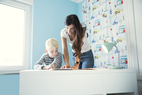 Mother helping son doing homework at desk - MFRF01207