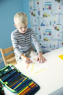 Boy drawing on paperk at desk in children's room - MFRF01222
