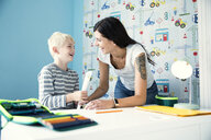 Mother and son having fun at desk in children's room - MFRF01225
