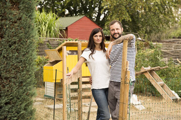 Portrait of confident couple standing at chickenhouse in garden - MFRF01264