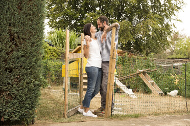 Happy couple standing at chickenhouse in garden - MFRF01267