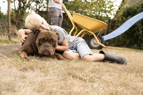 Deutschland, NRW, Garten, Hund, Old English Bulldog, Junge kuschelt sich an Hund der auf der Wiese liegt, im Hintergrund steht Vater mit der Schubkarre - MFRF01273