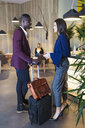 Business people waiting with luggage in hotel lobby - JSRF00162