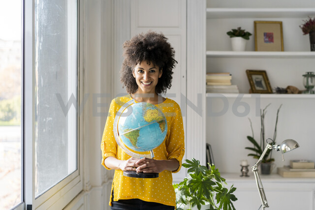 Beautiful woman holding globe, planning vacations - AFVF02543 - VITTA GALLERY/Westend61