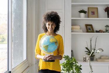 Beautiful woman holding globe, planning vacations - AFVF02543