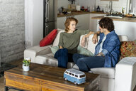 Couple sitting on couch, planning road trip - AFVF02549