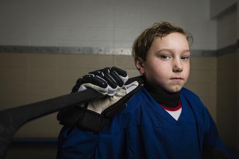 Portrait serious boy ice hockey player in uniform holding hockey stick - HEROF26279