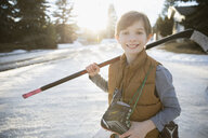 Portrait smiling boy holding ice hockey stick and ice skates on sunny, snowy road - HEROF26297