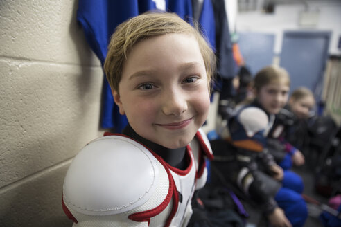 Portrait smiling boy ice hockey player in protective sportswear in locker room - HEROF26300