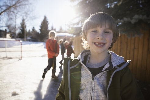 Portrait smiling boy playing ice hockey in sunny, snowy driveway - HEROF26306