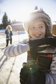 Portrait smiling girl with braces playing ice hockey in sunny, snowy driveway - HEROF26309
