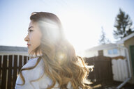 Serious young Chinese woman looking away in sunny driveway - HEROF26327