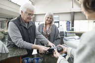Senior couple paying entrance fee with credit card at museum cashier - HEROF26357