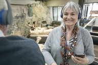 Portrait smiling senior woman wearing headphones at exhibit in war museum - HEROF26360