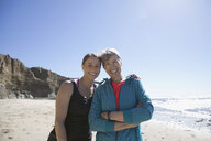 Portrait smiling mother and daughter hugging on sunny beach - HEROF26420