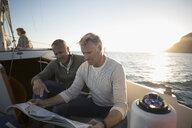 Senior men viewing map on sunset sailboat - HEROF26447