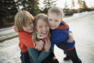 Portrait playful sons hugging mother on snowy road - HEROF26492