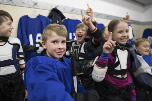 Portrait confident boy and girl ice hockey players cheering and celebrating in locker room - HEROF26498