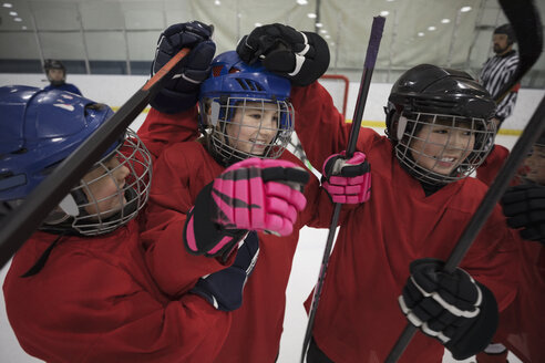 Playful boy and girl ice hockey players celebrating - HEROF26507