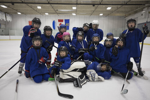 Portrait enthusiastic boy and girl ice hockey team on ice hockey rink - HEROF26513