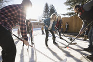 Parents playing ice hockey in sunny, snowy driveway - HEROF26516