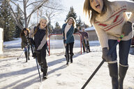 Playful mothers and daughter playing ice hockey in sunny, snowy driveway - HEROF26519