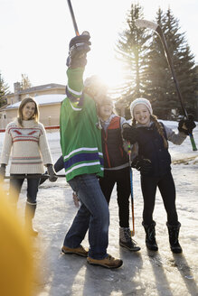 Portrait playful family playing ice hockey in sunny, snowy driveway - HEROF26522