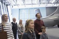 Multi-generation family looking at airplanes in war museum hangar - HEROF26591