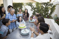 Multi-generation family celebrating birthday with cake and candles on patio - HEROF26621